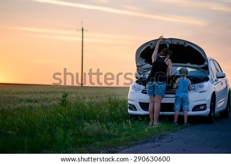 Rear View of a Mother and Son Repairing Something on their White Car at the Grassy Street Side on One Afternoon. - stock photo