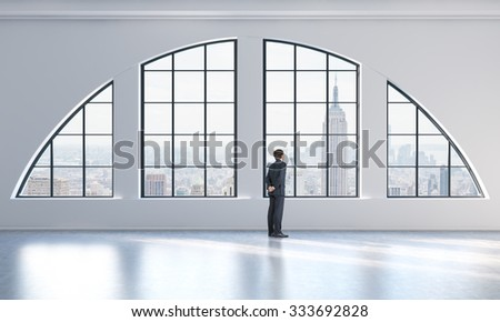 Rear view of a person in formal suit who is looking out the window in a modern loft interior. New York city view. - stock photo