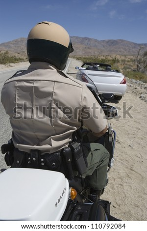 Rear view of a police officer riding motorcycle with car in the background - stock photo