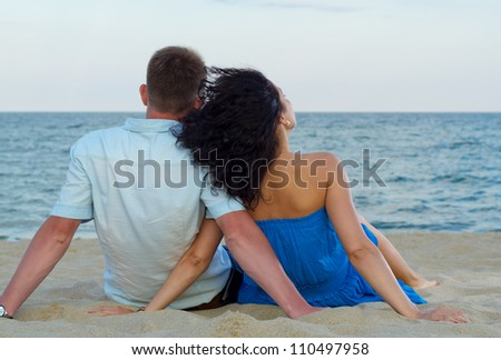 Rear view of a romantic couple sitting in the sand on a tropical beach admiring the ocean - stock photo