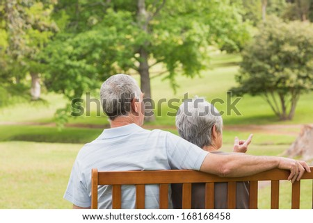 Rear view of a senior man and woman sitting on bench at the park - stock photo