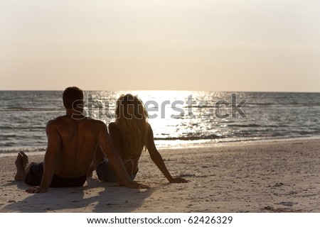 Rear view of a sexy and attractive young man and woman couple sitting on a beach looking out to see at sunset - stock photo