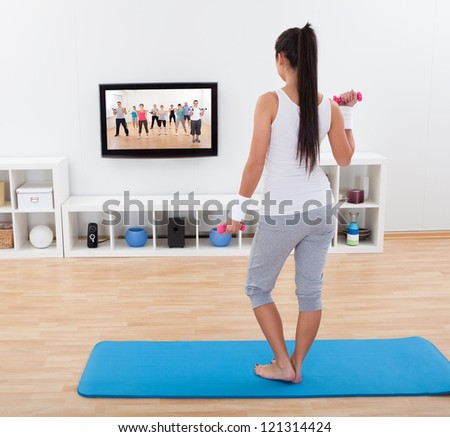 Rear view of a shapely barefoot young woman working out with dumbbells standing on a mat in her living - stock photo