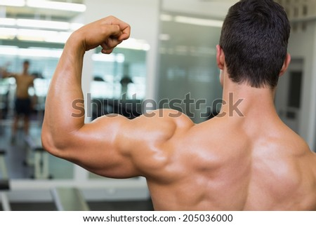 Rear view of a shirtless muscular man flexing muscles in gym - stock photo