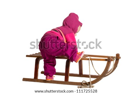 Rear view of a small toddler dressed in colorful winter woollies clambering onto a traditional wooden winter sled isolated on white - stock photo