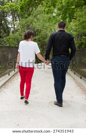 Rear view of a smiling couple holding hands and walking on country road