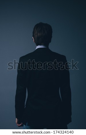 Rear view of a stylish businessman standing facing away from the camera with his arms at his side over a dark grey background - stock photo