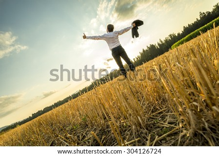 Rear View of a Successful Young Businessman Standing at the Field with Wide Open Arms and Looking Up in the Sky. - stock photo