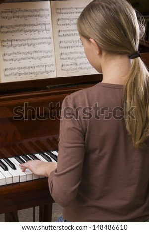 Rear view of a teenage girl playing the piano - stock photo