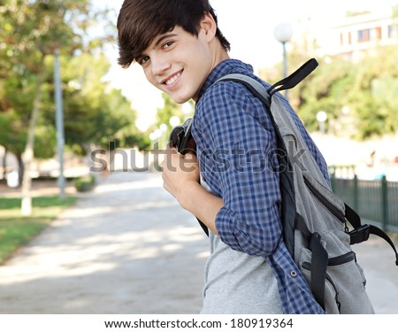 Rear view of a teenager student boy walking on a path at a college campus grounds carrying a backpack and turning to smile at the camera joyfully. Student lifestyle outdoors. - stock photo