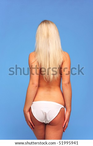 Rear view of a topless blond woman wearing bikini bottoms