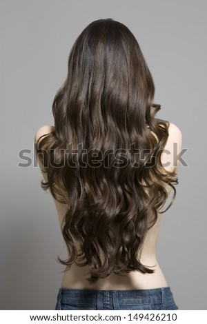 Rear view of a topless woman with long brown wavy hair against gray background - stock photo