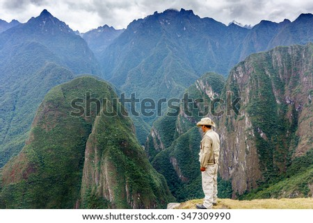 Rear view of a tourist looking at mountains view in Machu Picchu, Cusco Region, Urubamba Province, Machupicchu District, Peru - stock photo
