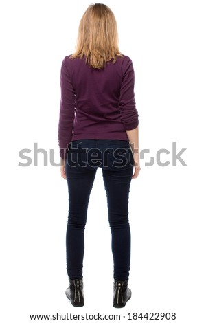 Rear view of a trendy slender modern young woman in close fitting pants standing with her legs apart, isolated on white