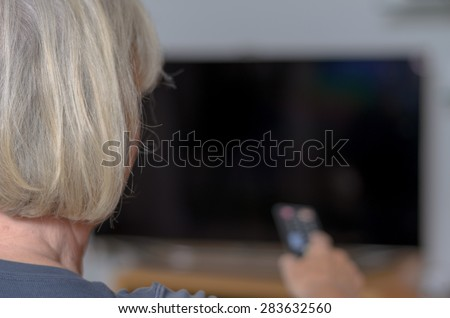 Rear View of a White Haired Middle Aged Woman Sitting at the Living Area While Controlling the TV Using a Remote Control Device.