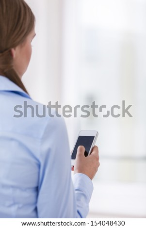 Rear View of a Woman holding a smart phone - stock photo