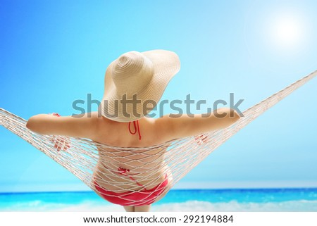 Rear view of a woman in a red swimsuit with a stylish hat lying on a hammock on a beach by the sea - stock photo