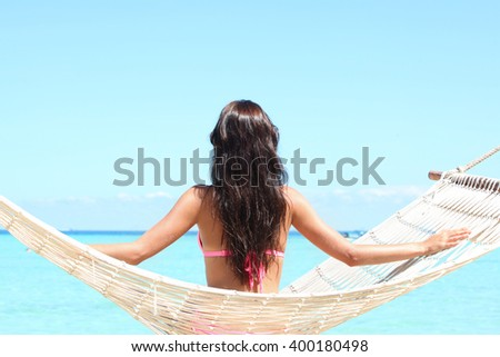 Rear view of a woman in bikini sitting on a hammock on a beach by the sea - stock photo