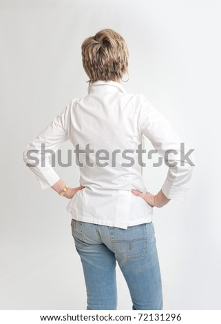 Rear view of a woman looking at something with hands on her hips - stock photo