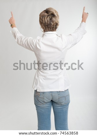 Rear view of a woman pointing at something with both hands