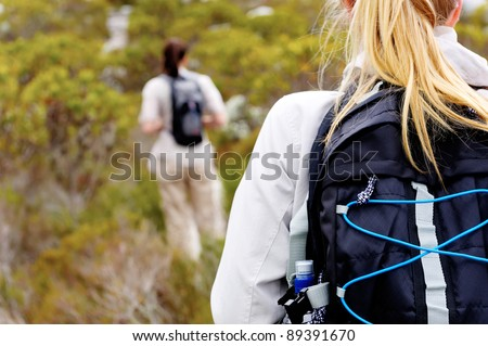rear view of a woman trekking outdoors with a backpack - stock photo
