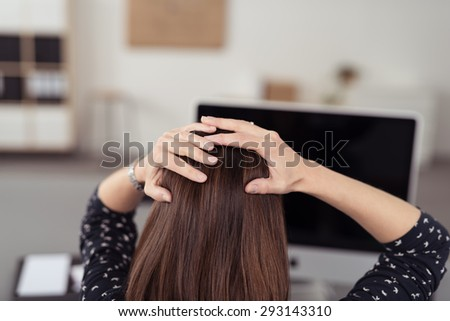 Rear View of a Worried Office Woman Holding her Head In Front her Powered Off Computer Due to Power Interruptions. - stock photo