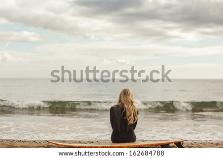 Rear view of a young blond in wet suit with surfboard at the beach - stock photo