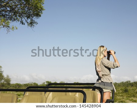 Rear view of a young blond woman on safari standing in jeep looking through binoculars - stock photo