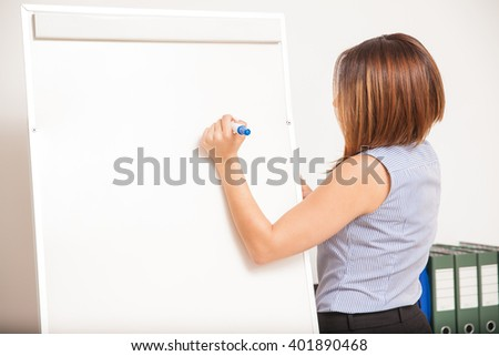 Rear view of a young brunette writing on a blank flip board in a classroom - stock photo