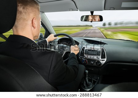 Rear View Of A Young Businessman Driving Car