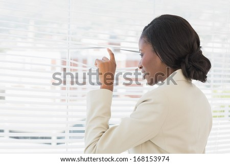 Rear view of a young businesswoman peeking through blinds in office