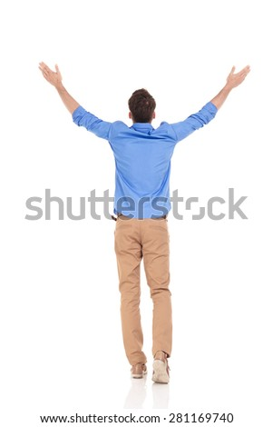 Rear view of a young casual man holding his hand up, celebrating a victory. - stock photo