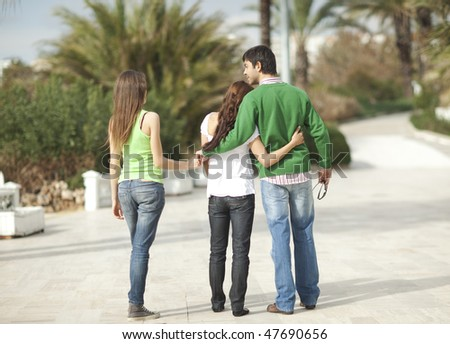 Rear view of a young couple embracing each other, man holding another woman's hand, palm trees in the background. - stock photo