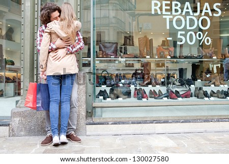 Rear view of a young couple hugging in a destination city while standing in the shopping district near a luxury shoe store, outdoors. - stock photo