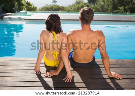 Rear view of a young couple sitting by swimming pool on a sunny day - stock photo