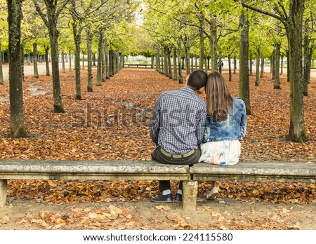 Rear view of a young couple sitting head in head on a bench in an urban park in autumn - stock photo