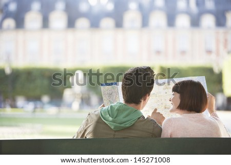 Rear view of a young couple sitting on bench and looking at map in park - stock photo