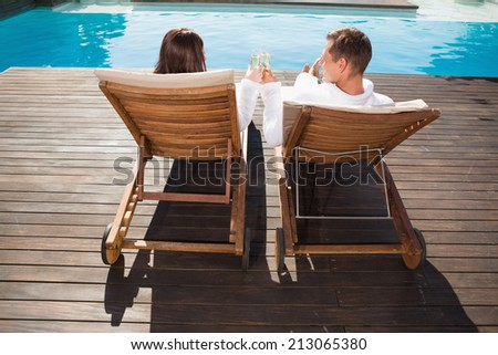 Rear view of a young couple toasting champagne by swimming pool - stock photo