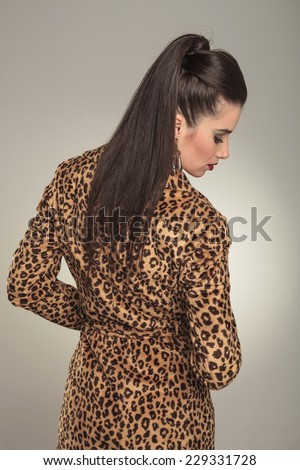 Rear view of a young fashion woman wearing a animal print coat, looking down.