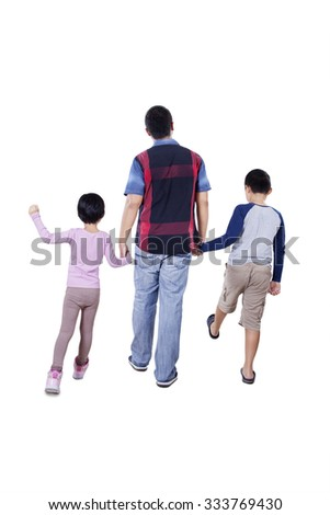 Rear view of a young father and his children holding hands in the studio and walking together - stock photo