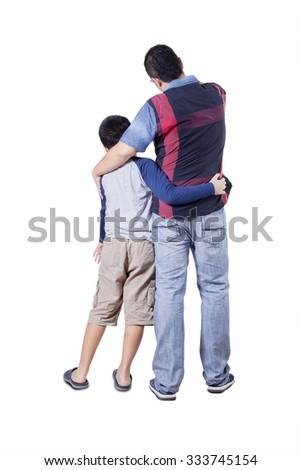 Rear view of a young father and his son embracing each other while looking at copy space in the studio - stock photo