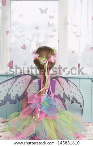 Rear view of a young girl in fairy costume looking through window - stock photo
