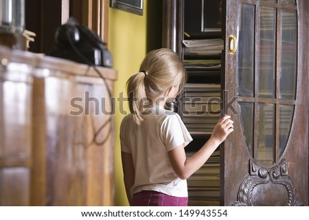 Rear view of a young girl opening cupboard door - stock photo