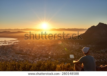 Rear view of a young guy sitting on a mountain trail watching the sunrise with the city below - stock photo