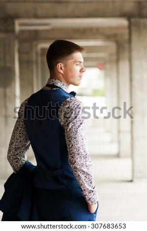 Rear view of a young handsome man in a flower shirt and vest outdoors.