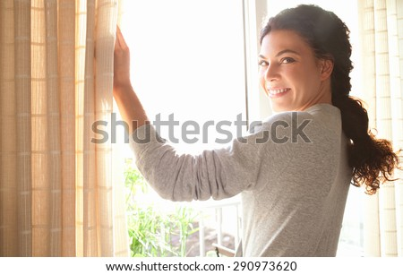 Rear view of a young joyful woman wearing robe and holding the curtains open to look out of large light window at home, turning to look and smile at camera, interior. Aspirational lifestyle indoors.