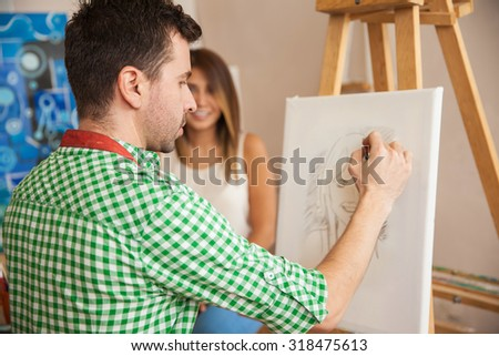 Rear view of a young male artist working on a portrait of a pretty female model in his studio