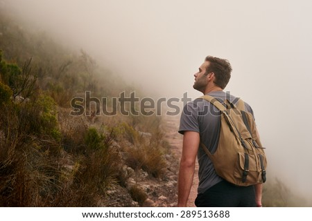 Rear view of a young man on a mountain trail looking up at the mountainside on a misty morning - stock photo