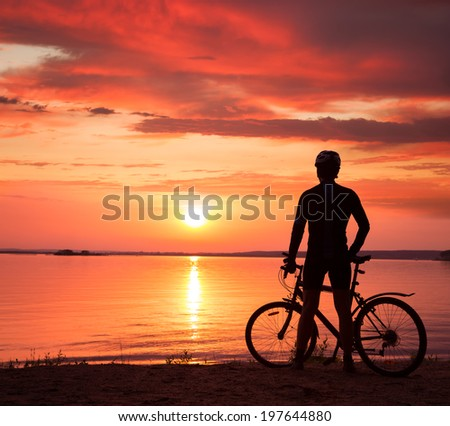 Rear View of a Young Man Standing with a Bicycle at Sunset. Healthy Lifestyle Concept. Copyspace. - stock photo