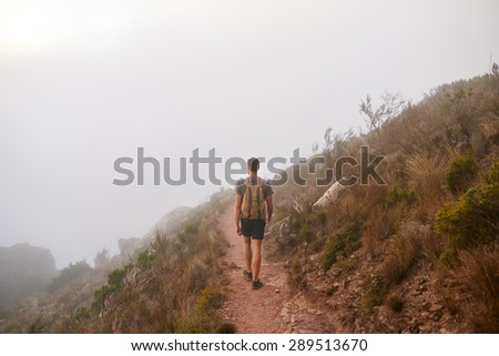 Rear view of a young man walking away from the camera into morning mist on a dirt path on a mountain nature trail  - stock photo